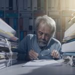 старый мужчина ищет с лупой в документах