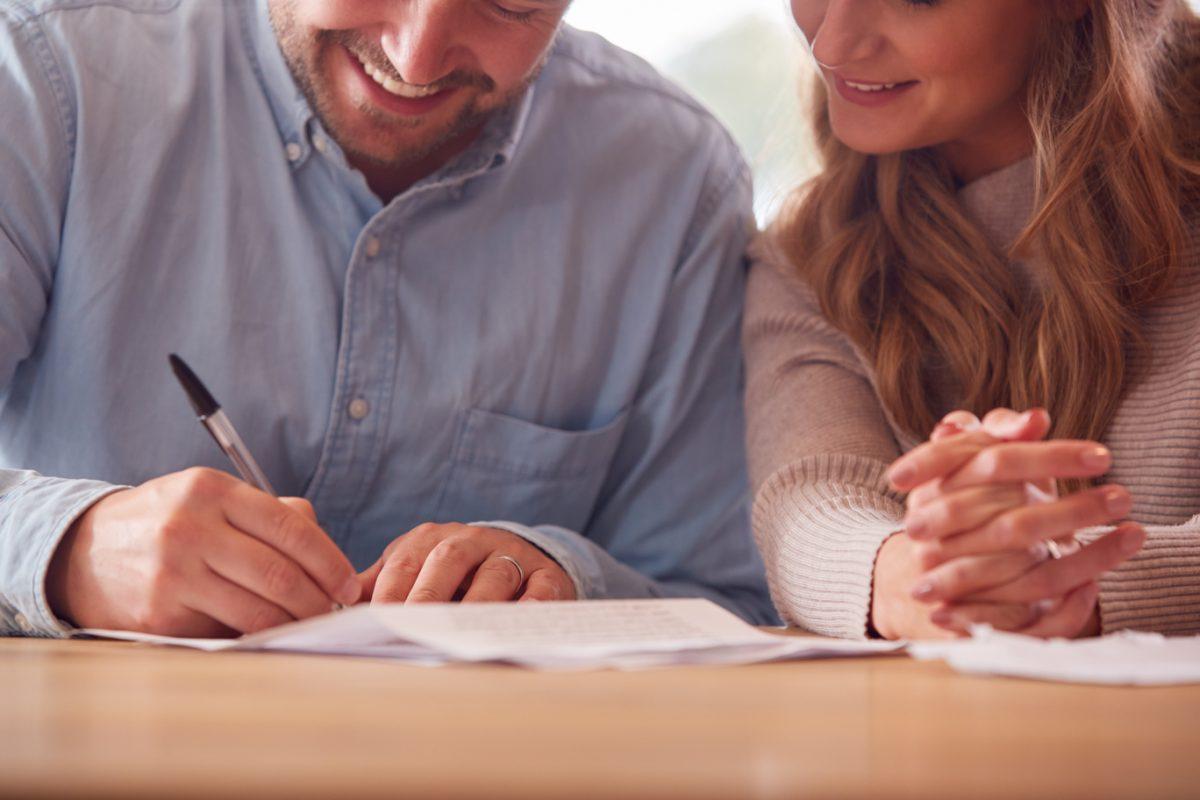 close up of smiling couple signing financial docum Основные причины, зачем нужен брачный договор и как его заключить