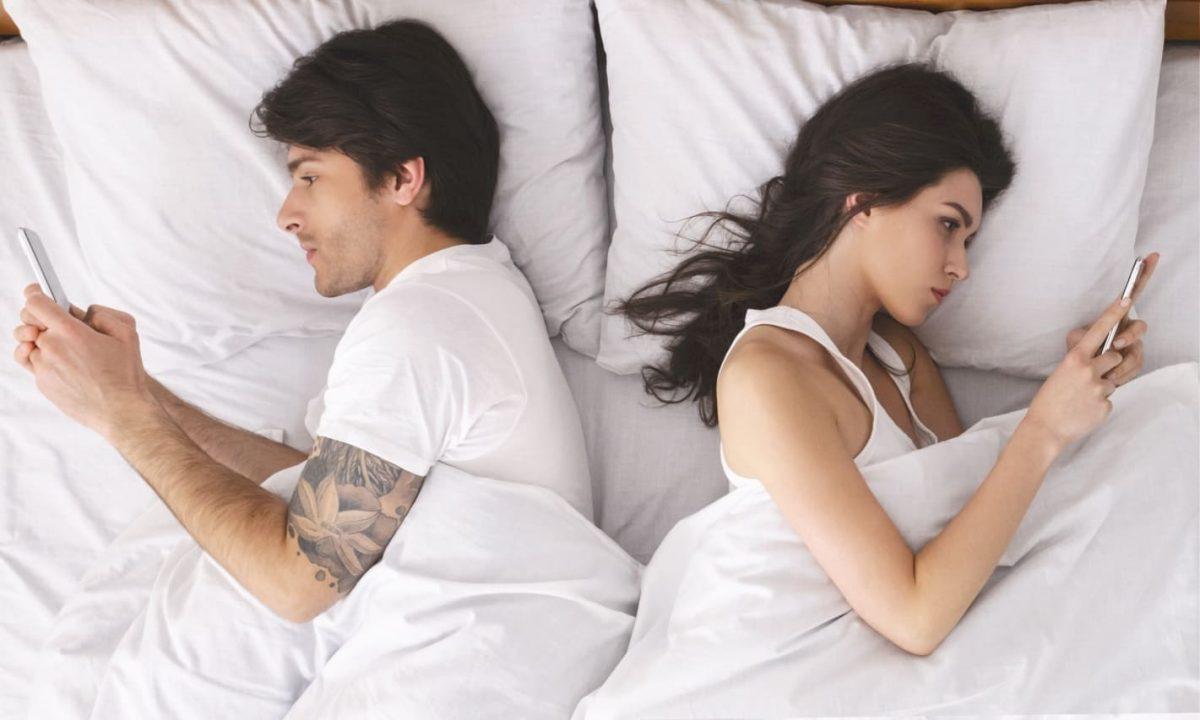 пара в ссоре лежат в кровати смотрят в телефоны